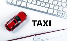 Röd bilmodell nära tangentbordet i begreppet av att kalla en taxi Arkivfoton