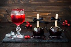 Röd blodig vampyrcoctail och svarta giftkaramelläpplen Traditionellt efterrättrecept för allhelgonaaftonparti Arkivfoton