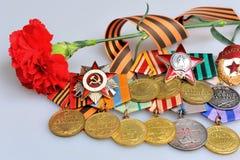Röd blomma med det St George bandet och militära utmärkelser av det stora patriotiska kriget Arkivfoto