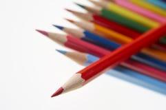 Röd blyertspenna överst av raden av färgade blyertspennor Royaltyfria Foton