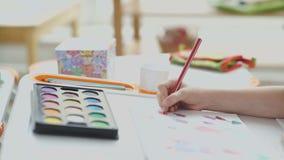 Röd blyertspenna för färg i barnhand Målarfärger och teckning på tabellen arkivfilmer