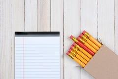 Röd blyertspenna i ask med anteckningsboken Royaltyfri Bild