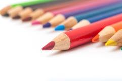 Röd blyertspenna i rad av den kulöra blyertspennanärbilden Arkivbilder