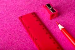 Röd blyertspenna med vässaren och linjal på röd bakgrund brevpapper arkivbild