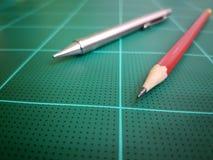 Röd blyertspenna- och silverpenna royaltyfria foton
