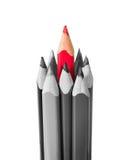 Röd blyertspenna som omges av svartvita blyertspennor Arkivbilder