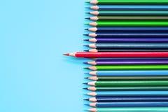 Röd blyertspenna som står ut på blå bakgrund Ledarskap unikhet, självständighet, insats, strategi, meningsskiljaktighet, tänker o royaltyfri bild