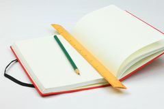Röd bok, blyertspenna och linjal royaltyfri fotografi