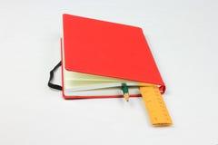 Röd bok, blyertspenna och linjal arkivbilder