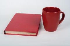 Röd bok och kopp på en vit tabell Kopiera utrymme för text Arkivbilder