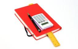 Röd bok, penna, räknemaskin och linjal royaltyfri foto