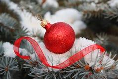 Röd boll för jul med bandet på jultree Arkivfoto