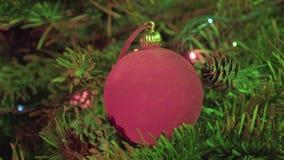 Röd boll för ` s för nytt år mot bakgrunden av den dekorerade girlanden av en julgran arkivfilmer