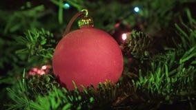 Röd boll för ` s för nytt år mot bakgrunden av den dekorerade girlanden av en julgran lager videofilmer