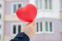 Röd boll-hjärta flicka som rymmer i hennes hand på bakgrunden av det stads- vinterlandskapet gåva med förälskelse på valentin dag royaltyfri foto