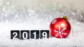 Röd boll och nytt år 2019 för jul, på snö, abstrakt bokehljusbakgrund arkivbilder