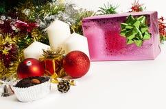 Röd bolljulgarnering och rosa giftbox på vita bakgrunder royaltyfri fotografi