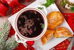 Röd borscht och bakelser för julhelgdagsafton Arkivfoto