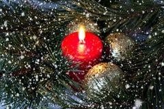 Röd bränningstearinljus och guld- julbollar med en granfilial under gående snö fotografering för bildbyråer