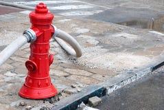 Röd brandpost som är i bruk Royaltyfri Foto