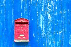 Röd brevlåda på den texturerade väggen Royaltyfri Foto
