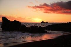Röd brinnande solnedgång på den svarta sandiga stranden med det enkla fartyget Arkivfoto