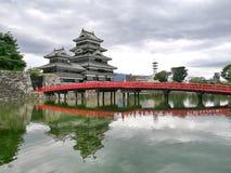 Röd bro med den Matsumoto slotten Royaltyfri Bild