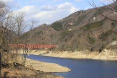 Röd bro som korsar floden arkivbilder