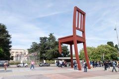 Röd bruten stol framme av det eniga nationhögkvarterkontoret i Genève fotografering för bildbyråer