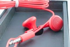 Röd bunden hörlurar Arkivbild
