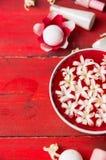 Röd bunke med vita blommor i vatten, flaska med lotion på trätabellen, brunnsortbakgrund Arkivbild