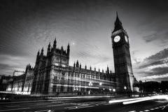 Röd buss, Big Ben och Westminster slott i London, UK på natten svart white Fotografering för Bildbyråer