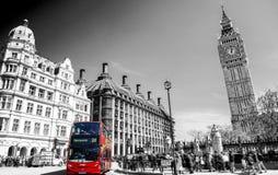 Röd buss i Lodon gatasikt med Big Ben i panorama som är svartvit Royaltyfri Foto