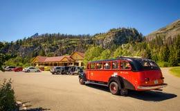 Röd buss med turister i glaciärnationalpark Royaltyfri Fotografi
