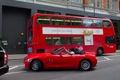 Röd buss och röd bil i London Arkivbilder