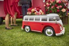 Röd bussbmw som dekoreras med rosor och ben av flickor i röda pläd bröllop Royaltyfri Fotografi
