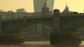Röd bussbortgång på den Southwark bron, stad av London i bakgrunden arkivfilmer