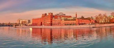 Röd byggnad med reflexion på floden Arkivbild