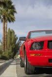 Röd cabriolet som parkeras av trottoarkanten Arkivfoto