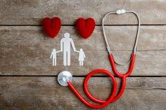 Röd chain familj för hjärta, för stetoskop och för papper på trätabellen Royaltyfri Fotografi