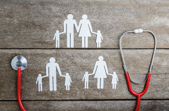 Röd chain familj för hjärta, för stetoskop och för papper på trätabellen Arkivbild