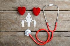 Röd chain familj för hjärta, för stetoskop och för papper på trätabellen Royaltyfri Bild