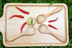 Röd chili, limefrukt och träsked mycket av ris Arkivfoto