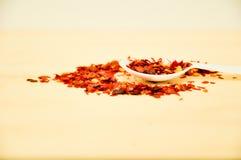 Röd chiliflinga med en vit sked Arkivfoton