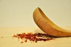 Röd chiliflinga med en wood sked som vänder mot upp royaltyfria bilder