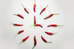 Röd chilipeppar tar tid på arkivfoton
