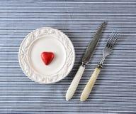 Röd chokladhjärta på plattor och kniven med en gaffel royaltyfri foto