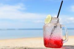 Röd coctail för sodavatten för citron för andedrink på stranden arkivfoto