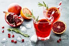 Röd coctail med blodapelsinen och granatäpplet Uppfriskande sommardrink Ferieaperitif för julparti Royaltyfria Bilder