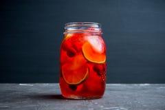 Röd coctail med körsbäret och limefrukt i krus på den lantliga bakgrunden fotografering för bildbyråer